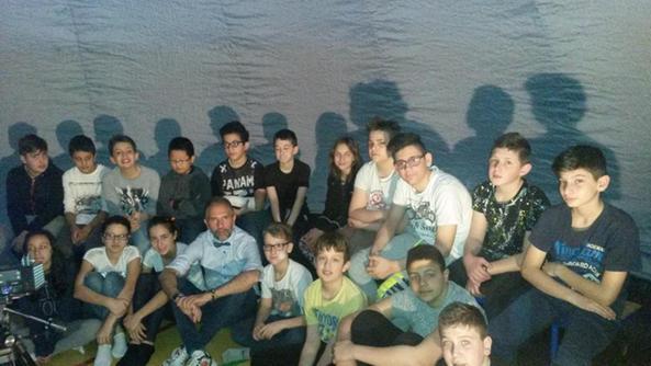Un gruppo di alunni nel planetario con al centro Gianluca Di Luccio