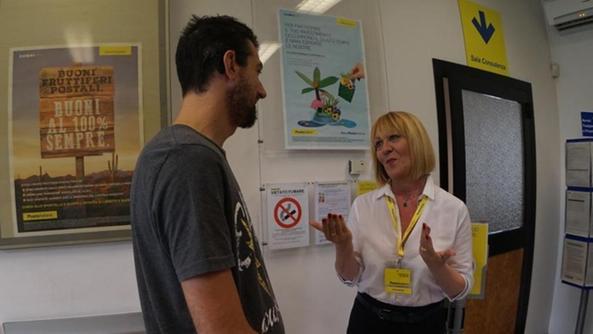 Antonella Manfrin comunica utilizzando la lingua dei segni con un utente dello sportello postale